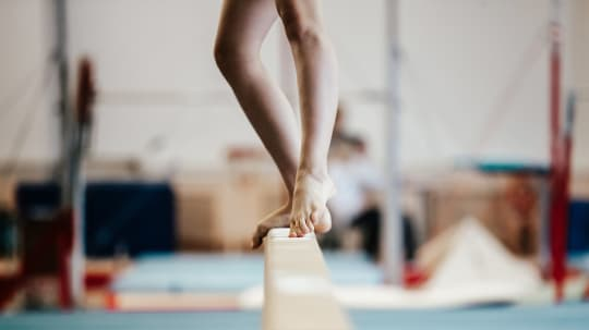 gymnast standing on a beam